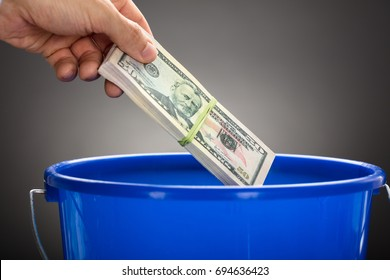 Cropped hand of businessman throwing US paper currency bundle in blue bucket against gray background