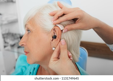 Cropped hand of doctor adjusting woman hearing aid, ear, close-up