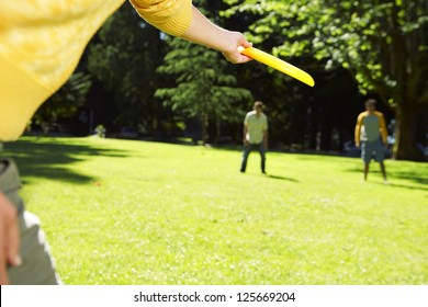 cropped hand in the foreground about to throw a frisbee to two people at the background, with trees in the background