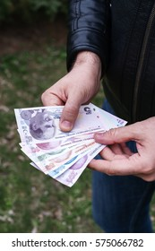 Cropped Hand Holding Turkish lira Paper Currency Over Street