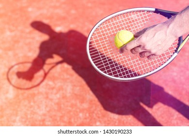 Cropped hand of mature man serving tennis ball on red court during sunny day