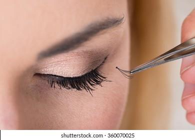Cropped hand putting false eyelashes on woman's eye