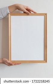 Cropped hand of woman holding picture frame against wall. Frame mock up.