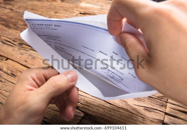 Cropped hands of businessman opening envelope with paycheck