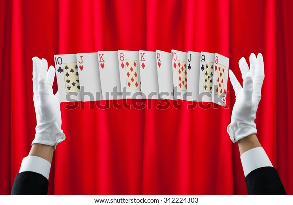 Cropped hands of magician performing trick with cards against red curtain