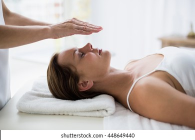 Cropped hands of therapist performing reiki on young woman at spa