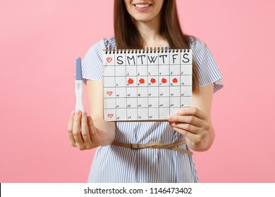 Cropped happy woman in blue dress, hat hold in hand pregnancy test, periods calendar for checking menstruation days isolated on pink background. Medical, healthcare, gynecological concept. Copy space