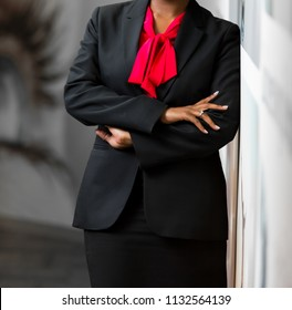 Cropped head African Business Woman in corporate attire with arms folded