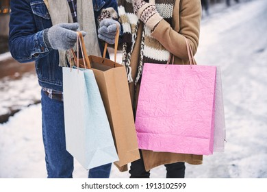 Cropped head of man and woman walking in snowy street in city and carrying paper bags with purchases