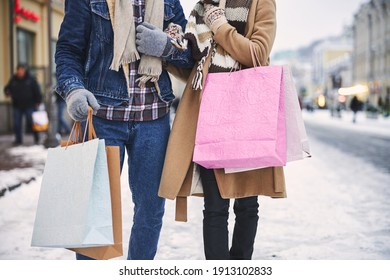 Cropped head of man and woman walking along snowy street in city and carrying paper bags