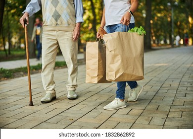 Cropped head portrait of old male with adult female walking through the city park with foodstuff in packages