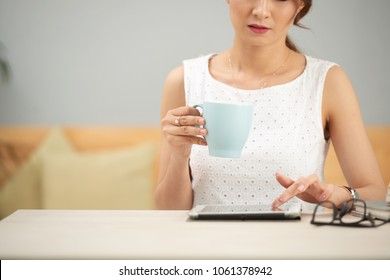 Cropped iamge of business woman drinking tea and reading e-mails on tablet computer
