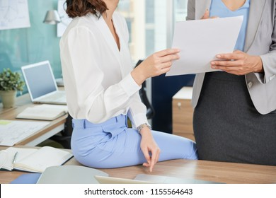 Cropped iamge of female colleagues discussing document at office table
