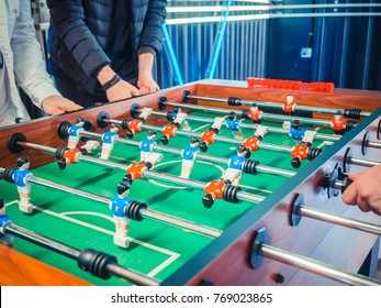 Cropped image of active people playing foosball. table soccer plaers. Friends play together table football