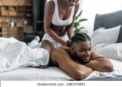 cropped image of african american girlfriend doing massage for boyfriend in bedroom
