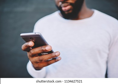 Cropped image of african american man holding modern smartphone dialing number, dark skinned male in white shirt using mobile phone for chatting in social networks via 4G internet connection outdoors