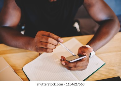 Cropped image of african american man holding digital gadget and stylus for making online booking, top view dark skinned man using smartphone and electronic pen signing bills in banking application