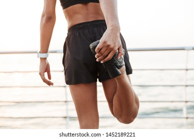 Cropped image of african american young woman in sportive clothes stretching her legs while doing workout by seaside in morning