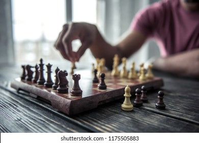 Cropped image of Afro American man playing chess, one angle of the chessboard in focus, on wooden table
