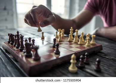 Cropped image of Afro American man playing chess, on wooden table