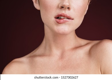 Cropped image of alluring shirtless woman with clean fresh face biting her lips isolated over red background