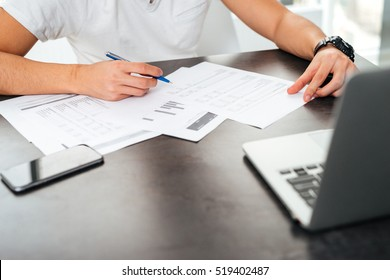 Cropped image of asian man by the table. with laptop, phone and documents