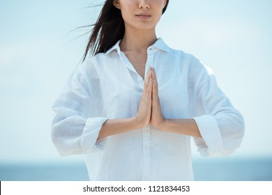 cropped image of asian woman doing namaste mudra gesture on beach