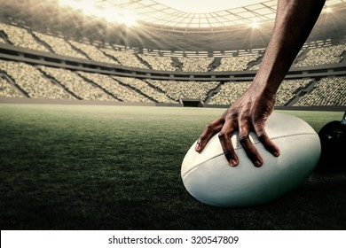 Cropped image of athlete holding rugby ball against rugby stadium
