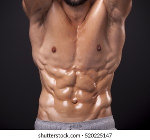 Cropped image of athletic man showing sixpack abs over black background