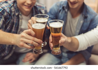Cropped image of attractive guys clinking glasses of beer and smiling while resting at home