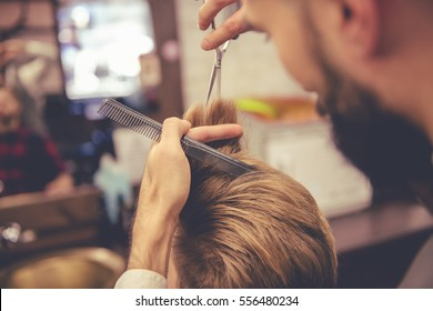Cropped image of attractive hairdresser cutting his handsome client's hair at the barbershop