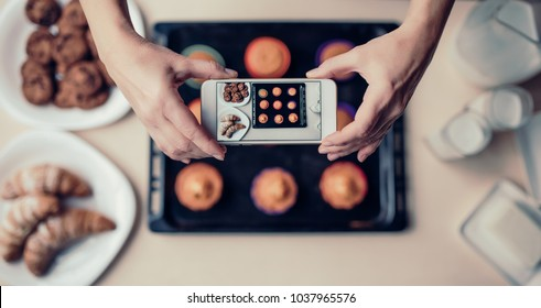 Cropped image of attractive senior woman is cooking on kitchen. Grandmother making tasty baking. Top view of woman making photo of food on a smart phone.