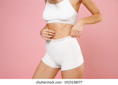 Cropped image of attractive young brunette woman 20s wearing white brassiere underwear with sports fit standing posing hold hands on belly stomach isolated on pastel pink background, studio portrait
