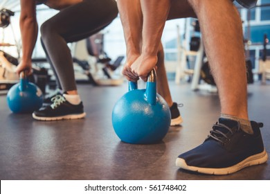 Cropped image of attractive young sports people working out with kettlebell in gym