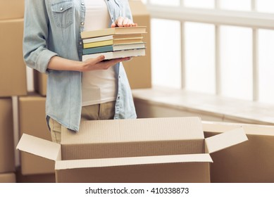 Cropped image of attractive young woman moving, packing books in cardboard box, looking at camera and smiling