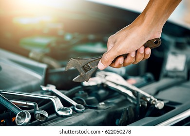 Cropped image of automobile mechanic repairing car in store, day time