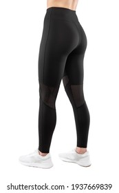 Cropped image of the back of a female model dressed in tight black leggings, isolated on a white background. Sportswear concept. Vertical view.
