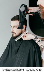 cropped image of barber drying customer beard at barbershop