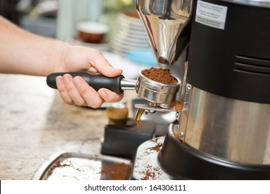 Cropped image of barista holding portafilter with ground coffee in cafe