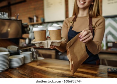Cropped image, barista is working in coffee shop, young woman is standing behind the bar counter, making coffee, take away.