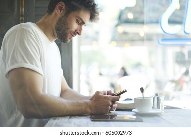 Cropped image bearded hipster guy check own mail and chatting with friends in social networks on mobile phone using free internet sitting in cafe shop with cup of coffee.  Advertising copy space area