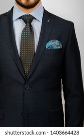 Cropped image of bearded male in black suit with tie and pocket square, isolated on gray. front view