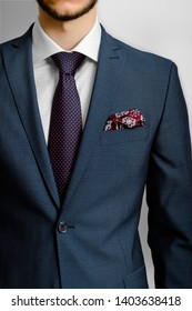 Cropped image of bearded male in a classic suit with tie and pocket square, isolated on gray