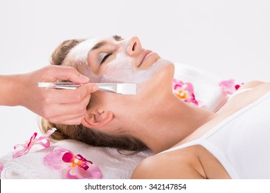 Cropped image of beautician applying mask on customer's face at salon