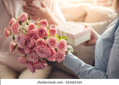 Cropped image of beautiful adult woman giving flowers and a gift box to her mature mother