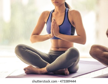 Cropped image of beautiful Afro American woman in sports clothes meditating in lotus position on mat while doing yoga