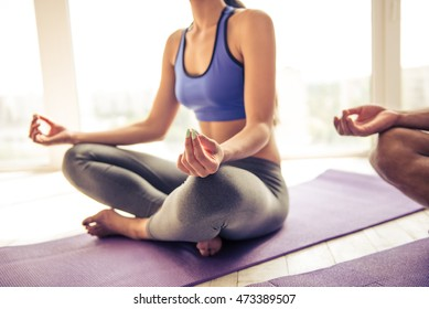 Cropped image of beautiful Afro American woman in sports clothes meditating in lotus position on mat while doing yoga at home