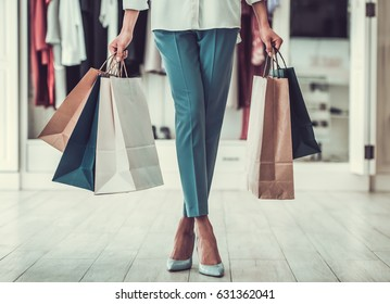 Cropped image of beautiful Afro American girl holding shopping bags while doing shopping in female boutique