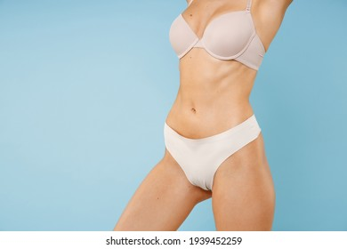 Cropped image of beautiful attractive fitness young brunette woman 20s in beige brassiere underwear showing perfect fit body standing posing isolated on pastel blue colour background, studio portrait