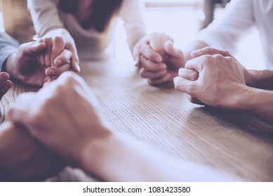 Cropped image of beautiful business team holding hands and praying while sitting in office